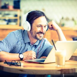 Handsome man wearing headphones using a laptop on a round, wooden table in a cafe
