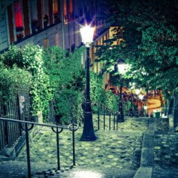 Night view looking down a wide set of public stairs in Paris that are beautifully lit by ornate street lamps