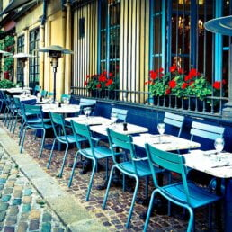 Blue cafe seats and small white dining tables on a cobbled street outside of a restaurant in Paris