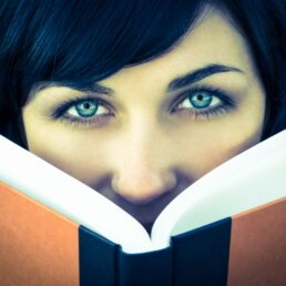 Beautiful lady with green eyes reading a brown book with a black binding